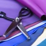 A pair of heavy, traditional pinking shears and fabric showing pinked edges