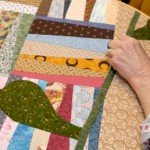 A crazy quilt, already pieced together, is quilted by hand. Crazy quilts can pieced by hand or machine and quilted by hand or machine.
