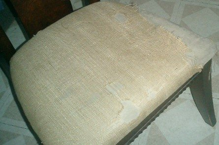 Someone had recovered the chair's dirty, worn original cover with burlap.  Notice how the burlap is now torn.